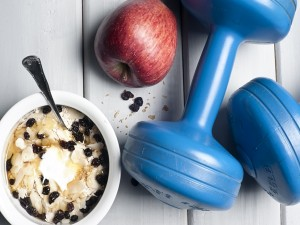 Dumbbells and red apple next to bowl with yogurt